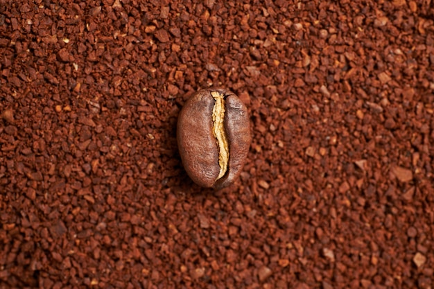 Graine de café sur le fond du café moulu.