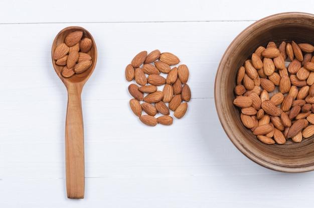 Graines d'amande dans un bol et cuillère en bois