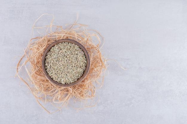 Graines d'anis vert dans une tasse en bois sur une surface en béton