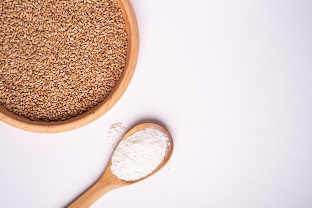 Graines de blé grains dans un bol en bois près de farine dans une cuillère spatule