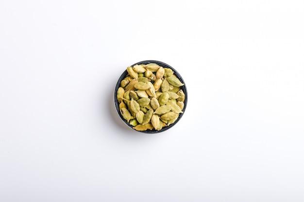 Graines de cardamome dans un bol sur fond blanc