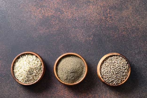 Graines de chanvre, farine, grains dans trois bols sur brun. vue de dessus.