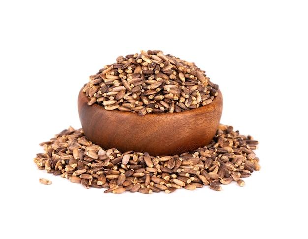 Graines de chardon-marie dans un bol en bois, isolé sur fond blanc