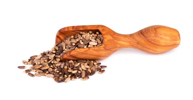 Graines de chardon-marie dans une cuillère en bois, isolé sur fond blanc.