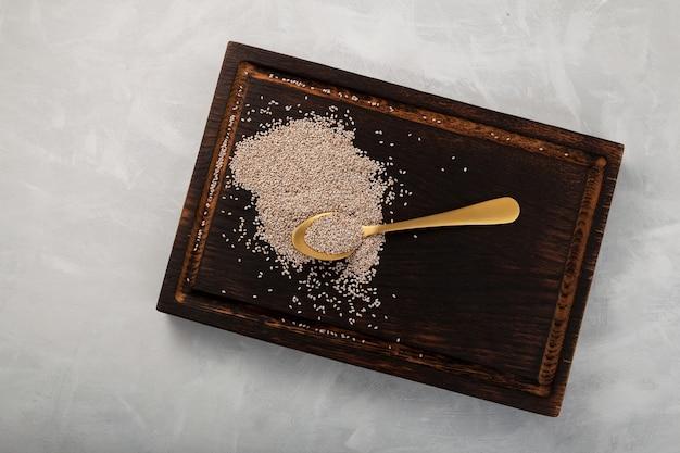 Graines De Chia Blanc Dans Une Cuillère Dorée Sur Une Planche à Découper En Bois Vue De Dessus Photo Premium