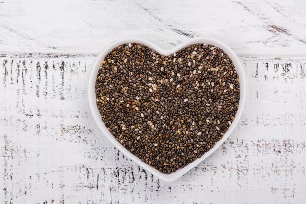 Graines de chia en bonne santé dans un bol en forme de coeur