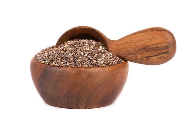 Graines de chia dans un bol en bois et cuillère, isolé sur fond blanc.