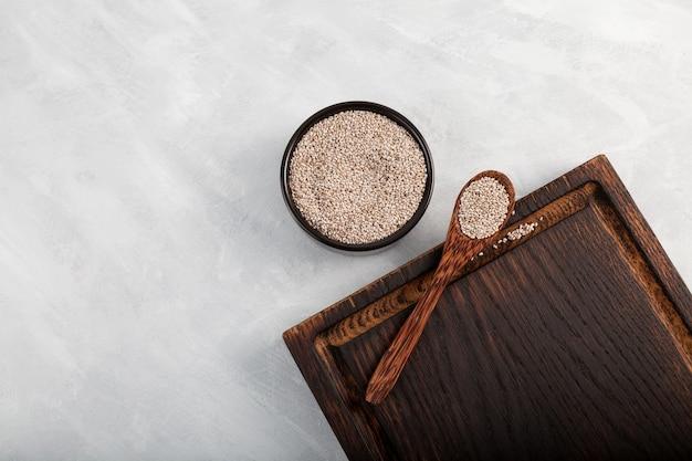 Graines de chia dans un bol noir avec une cuillère en bois et une planche à découper sur fond clair