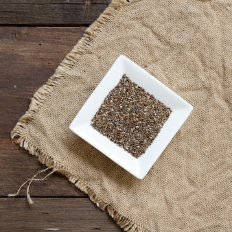 Graines de chia dans un bol sur la toile de jute sur une vue de dessus de fond en bois