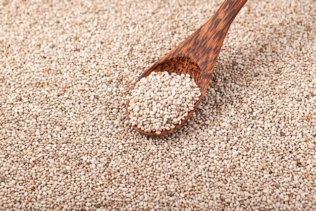 Graines de chia dans le fond de cuillère et de grains en bois