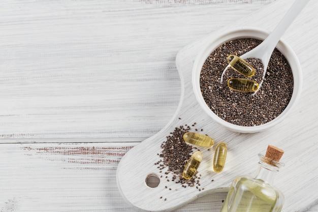 Graines de chia dans un petit bol et capsules de gélatine avec de l'huile oméga sur bois blanc. vue de dessus