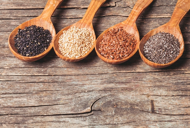 Graines de chia et de lin, sésame blanc et noir dans des cuillères en bois
