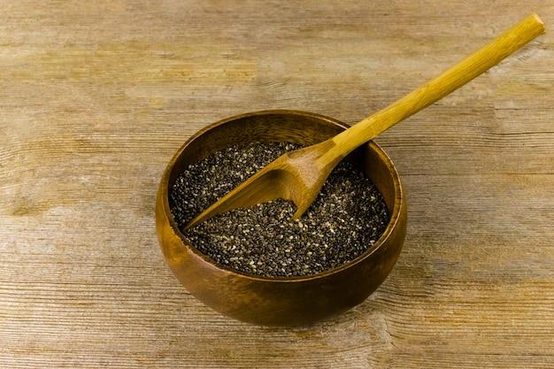 Graines de chia salvia hispanica dans un bol en bambou dans une cuillère en bois sur une vieille table en bois naturel. concept d'aliments sains, de superaliments et de suppléments. fermer. mise au point sélective. copier l'espace