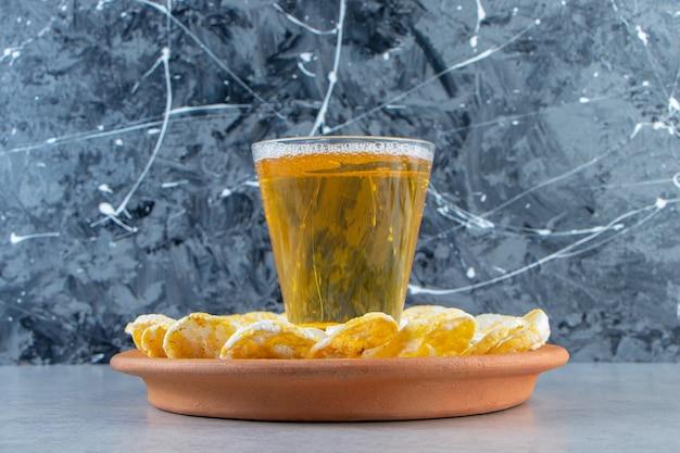 Graines, chips et pinte sur l'assiette, sur fond de marbre.