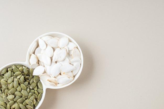 Graines de citrouille blanches et vertes dans des tasses blanches.