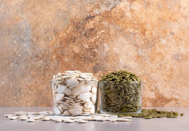 Graines de citrouille blanches et vertes sur fond de béton.