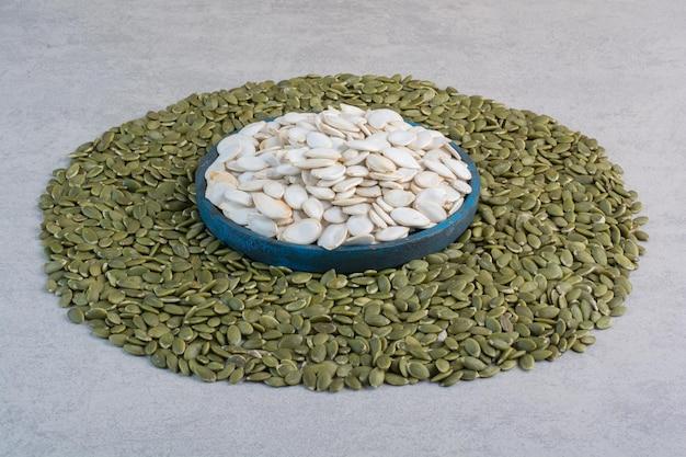 Graines de citrouille blanches et vertes sur une surface en béton.