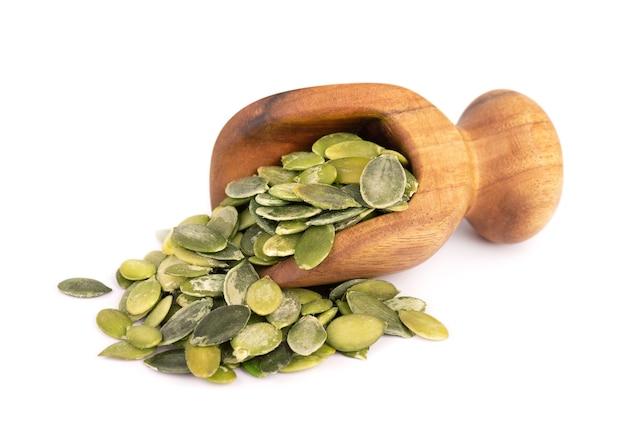 Graines de citrouille en cuillère en bois, isolé sur fond blanc. graines de pepita vertes.