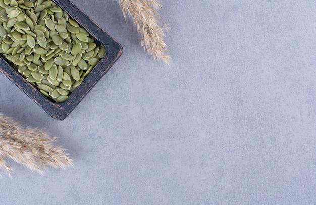 Graines de citrouille dans une assiette en bois à côté d'herbe de pampa sur marbre.