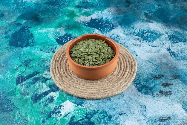 Graines de citrouille dans un bol sur dessous de plat, sur la table en marbre.