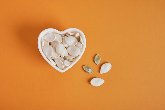 Graines de citrouille dans un bol en forme de coeur sur fond marron, espace pour copie de la vue de dessus