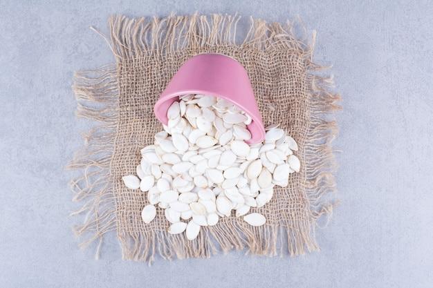 Graines de citrouille dans le bol renversé sur la serviette en toile de jute sur la surface en marbre