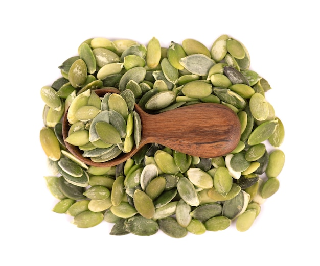 Graines de citrouille dans une cuillère en bois, isolé sur fond blanc. graines de pepita vertes. vue de dessus.