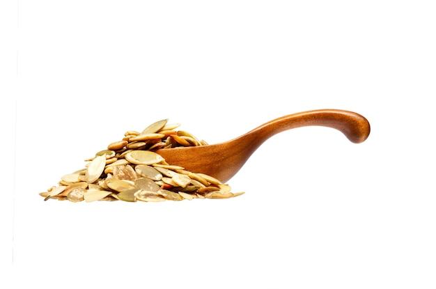 Graines de citrouille dans la cuillère en bois, isolées sur fond blanc. photo haute résolution.