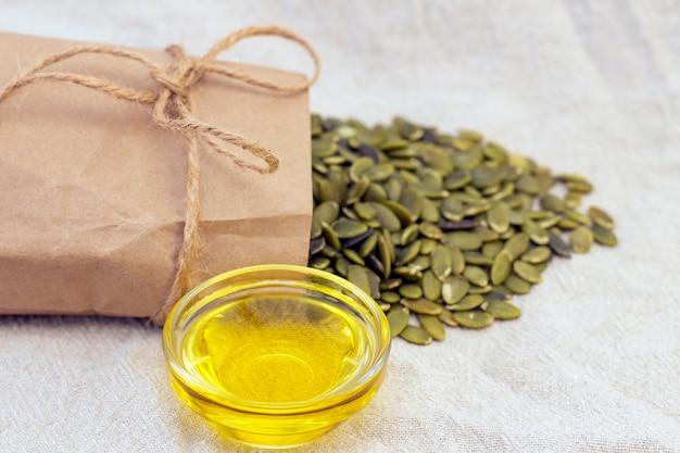 Graines de citrouille dans un sac en papier, huile de graines de citrouille sur lin naturel. graines de citrouille vitamines du groupe b et magnésium.