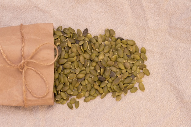 Graines de citrouille dans un sac en papier sur lin naturel. graines de citrouille vitamines du groupe b