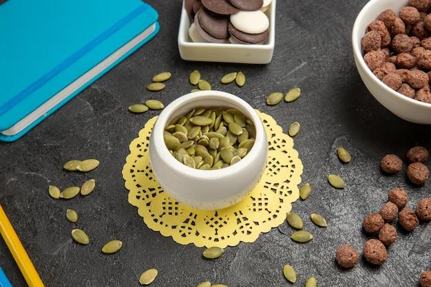Graines de citrouille fraîches avec des biscuits sur fond gris foncé bonbons aux graines de couleur arc-en-ciel