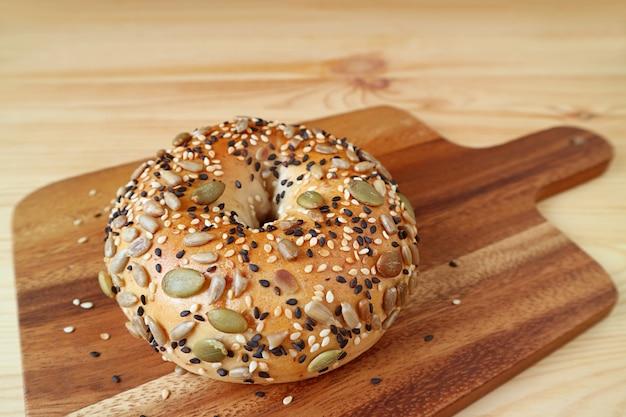 Graines de citrouille et graines de tournesol avec bagel au sésame sur planche à pain en bois