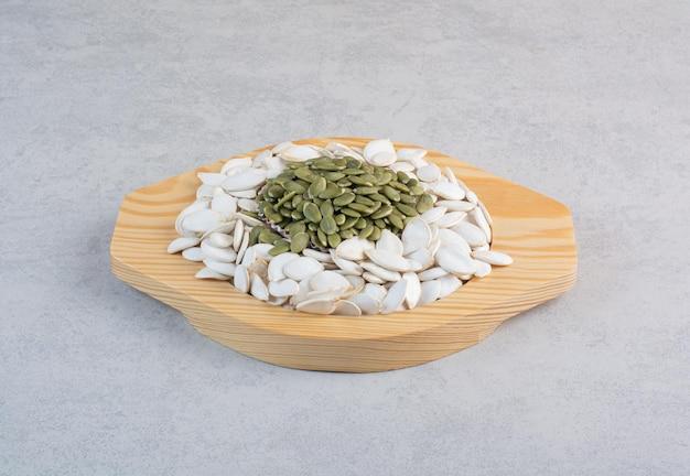 Graines de citrouille nettoyées et blanches vertes sur une surface en béton.