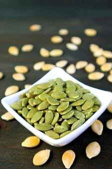 Graines de citrouille rôties avec des graines crues éparpillées sur une table en bois