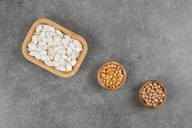 Graines de citrouille savoureuses, grains de maïs et pois sur marbre.