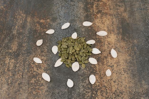 Graines de citrouille sur une surface en marbre.