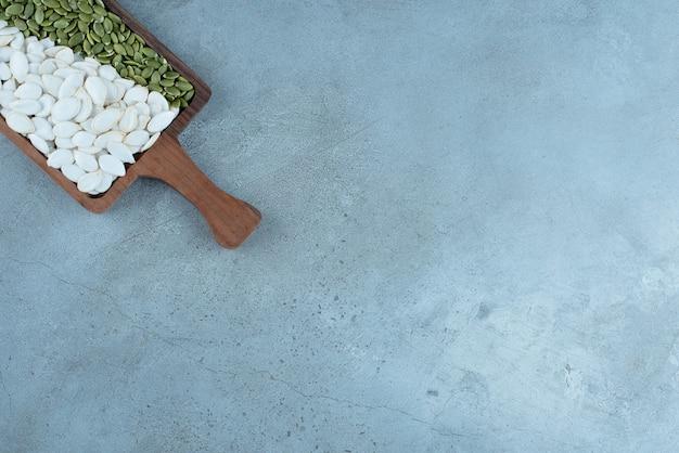 Graines de citrouille vertes blanches et nettoyées sur un plateau en bois. photo de haute qualité