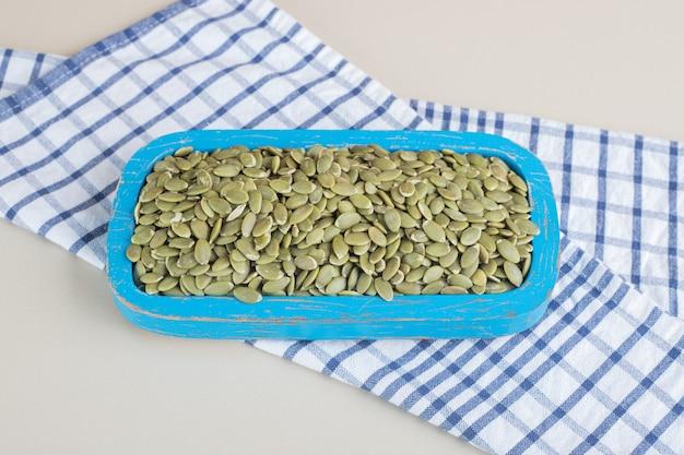 Graines de citrouille vertes dans un récipient sur béton.
