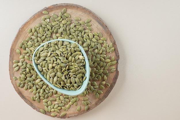 Graines de citrouille vertes dans une tasse en céramique sur béton.