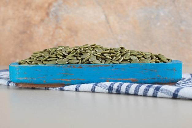 Graines de citrouille vertes isolées sur béton.