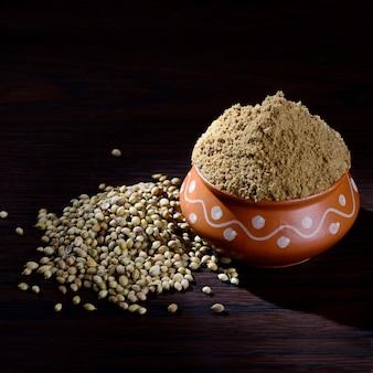 Graines de coriandre et coriandre en poudre dans un pot en argile sur fond de bois.
