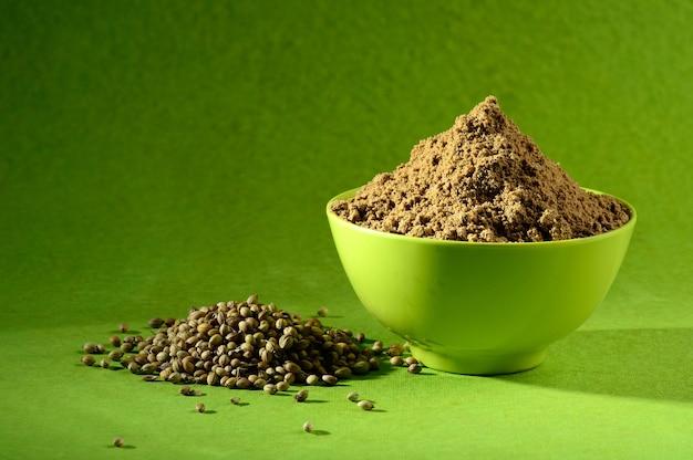Graines de coriandre et coriandre en poudre dans un récipient vert sur fond vert
