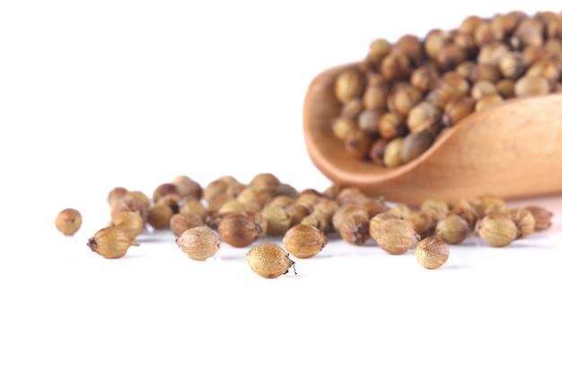 Les graines de coriandre fendues sont isolées sur un fond blanc.