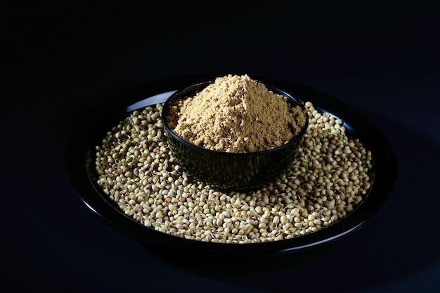Graines de coriandre et poudre sur surface noire