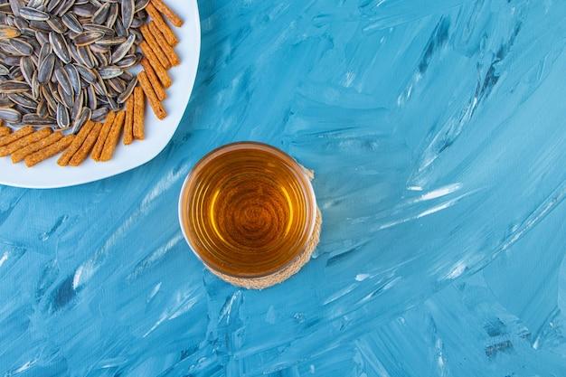 Graines et croûtons sur une assiette à côté d'une chope de bière, sur fond bleu.