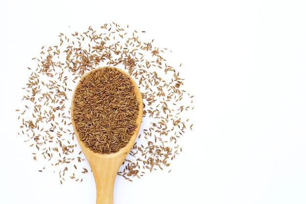 Graines de cumin ou de carvi sur une surface blanche.