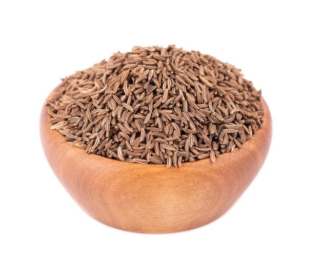 Graines de cumin dans un bol en bois, graines de cumin isolées ou carvi.