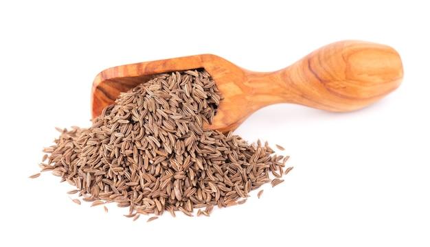 Graines de cumin dans une cuillère en bois, graines de cumin isolées ou carvi.