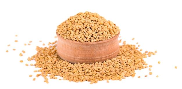 Graines de fenugrec dans un bol en bois, isolés