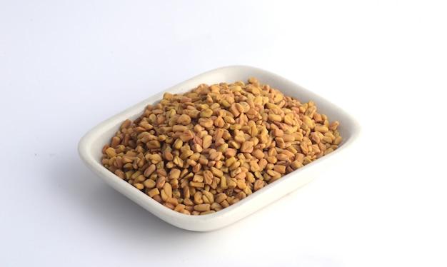 Graines de fenugrec en plaque blanche isolé
